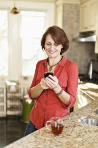 Woman using cell phone at home